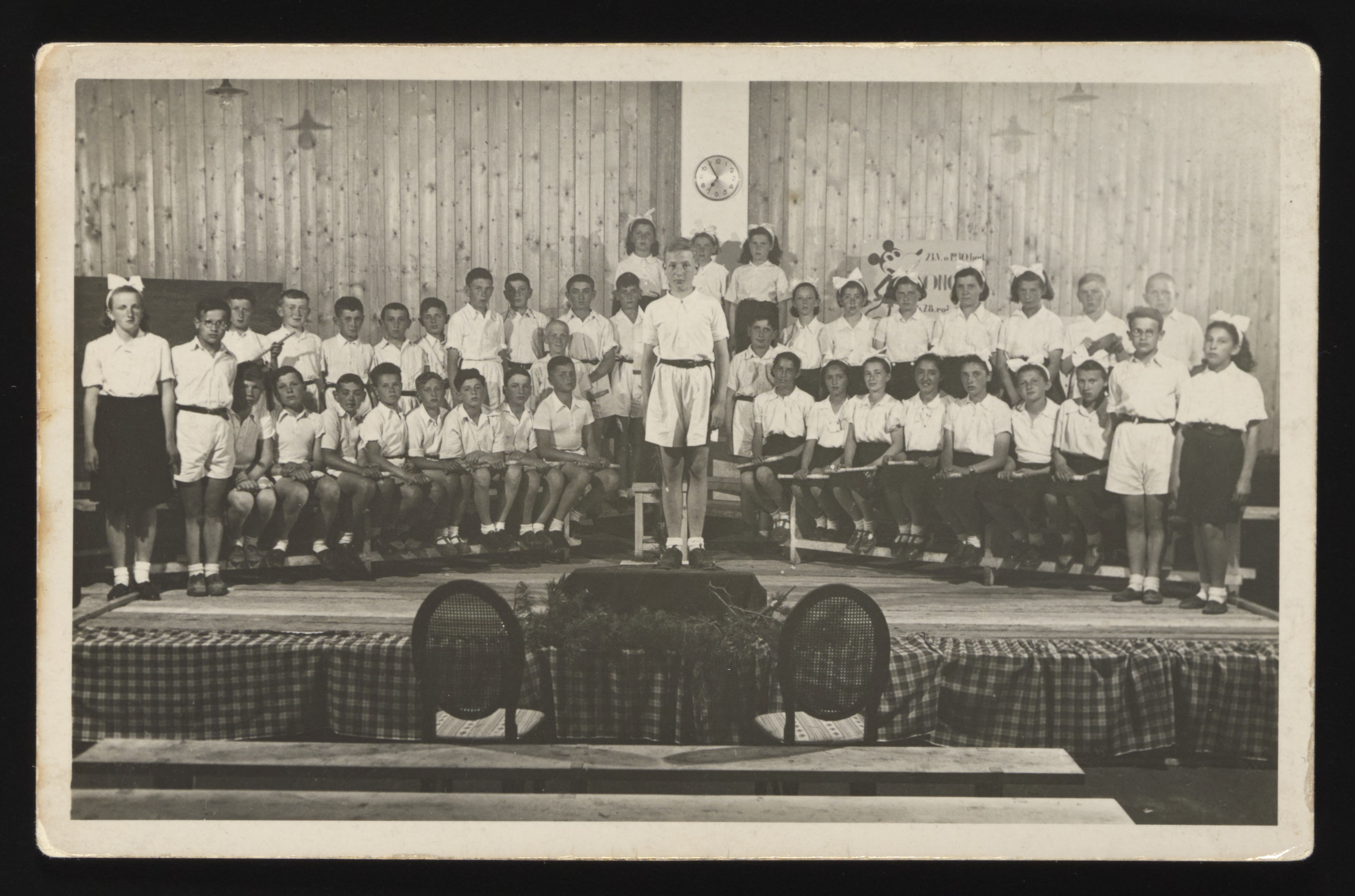 A large group of children put on a school performance at a Slovak labor camp.  The young boy standing in the front, center was later killed at Auschwitz.