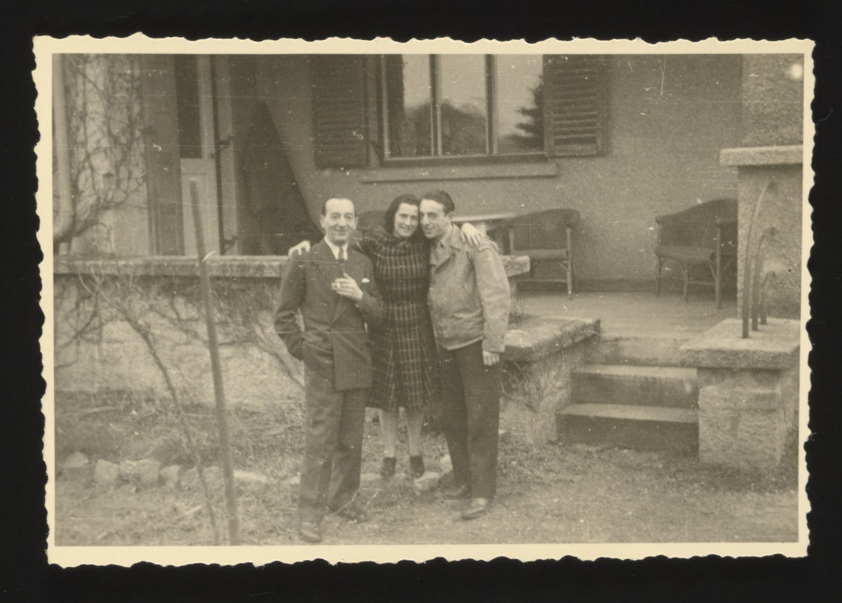 Boris, Jenny and Abba Buckhantz stand outside a building in the Deggendorf displaced persons camp.