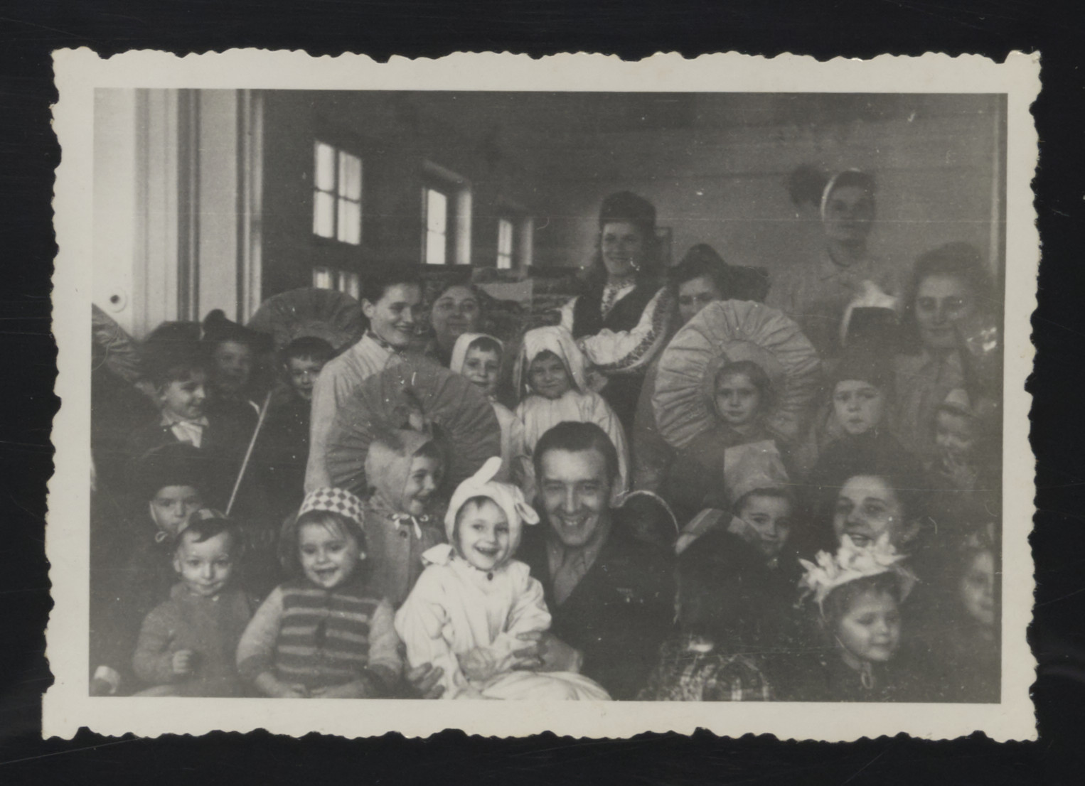 UNRRA director William Buckhantz meets with young children at a Purim celebration in the Deggendorf displaced persons camp.