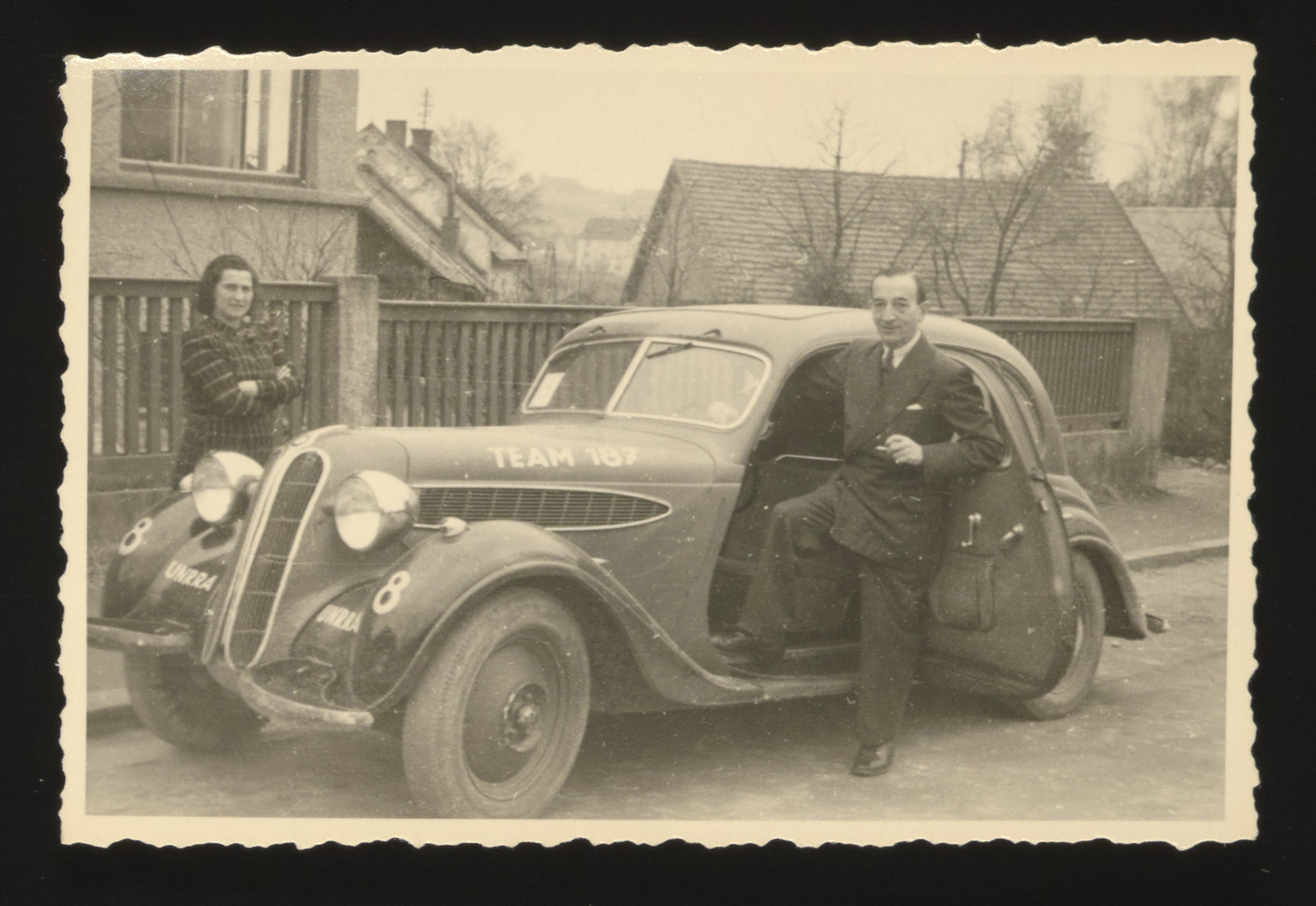Boris and Jenny Buckhantz stand next to the UNRRA staff car in the Deggendorf displaced persons camp.