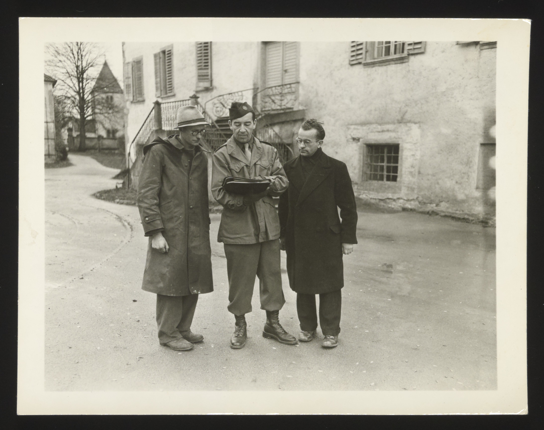 """William Buckhantz examines documents flanked by two displaced persons from Lithuania.  Original caption reads """"William Buckhantz, UNRRA deputy driector in front of Regendorf Castle with two Lithuanian engineers working on improvements."""""""