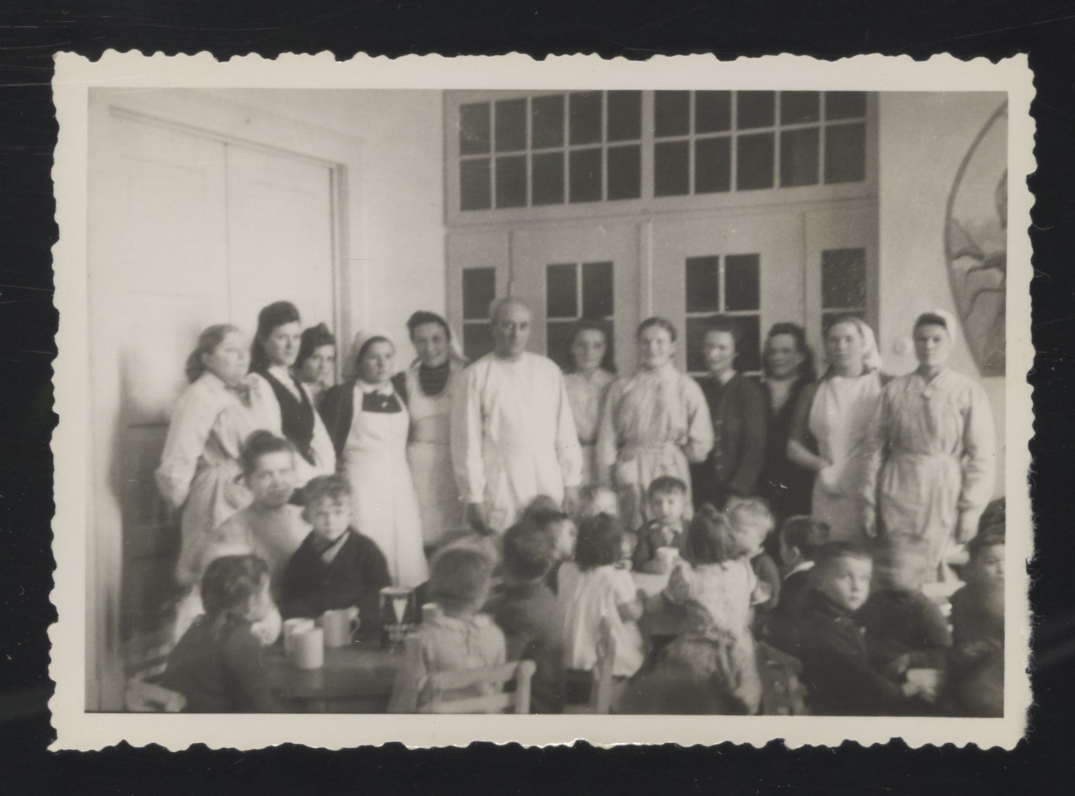 Staff of a kindergraten [probably in the Deggendorf displaced persons camp] stands behind young children who are sitting down for a meal.