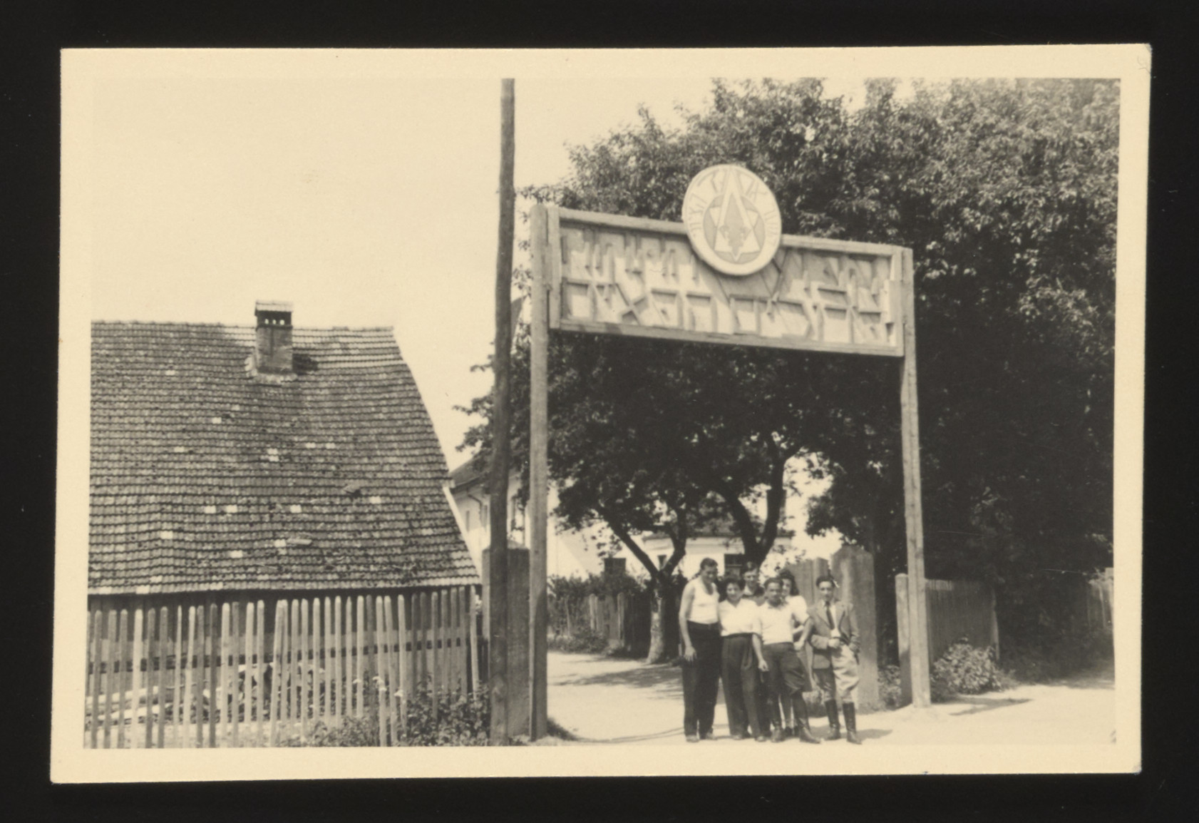 A group of young Jewish displaced persons poses underneath the welcome sign to an unidentified kibbutz hachshara.