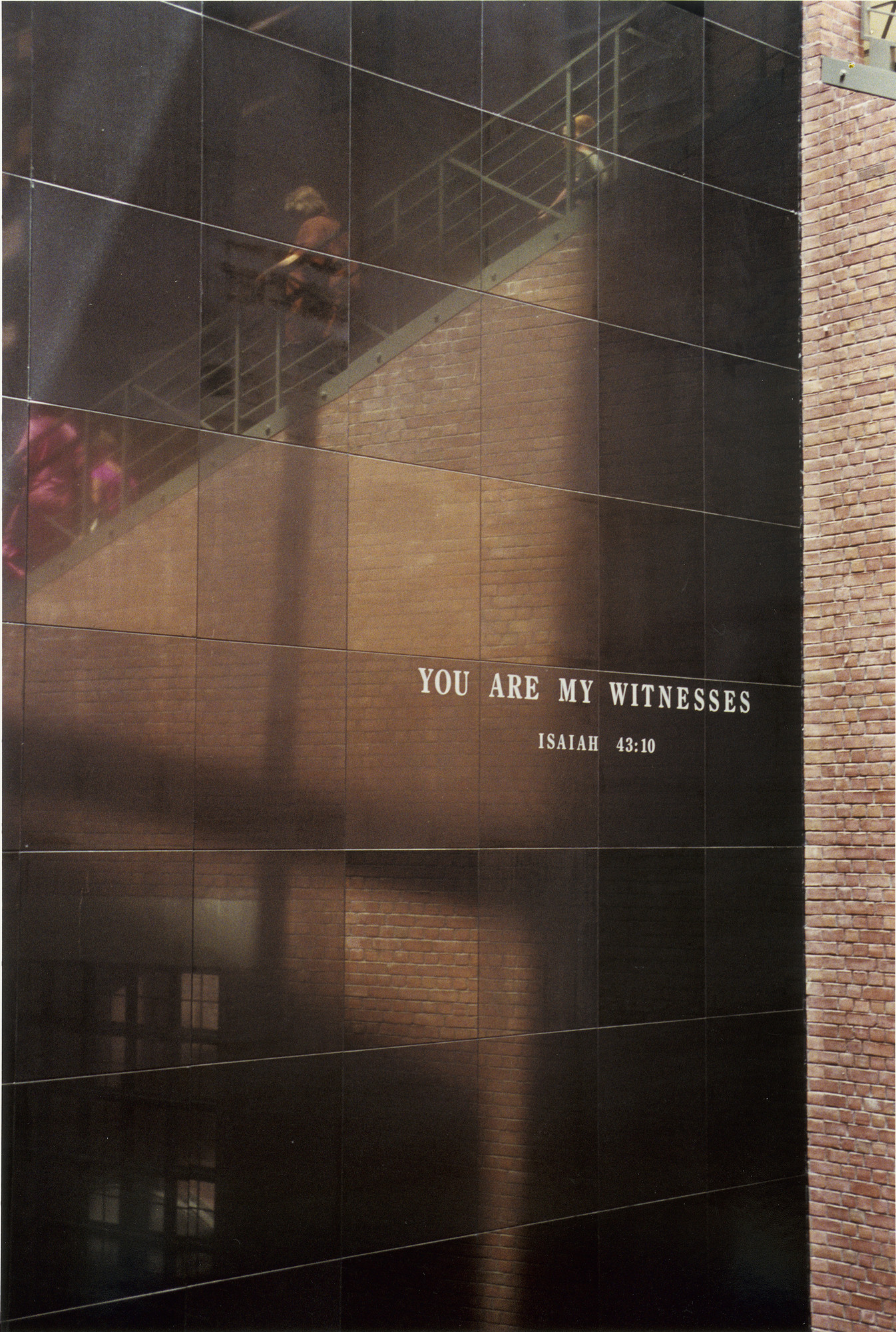 """Black granite wall bearing the quote """"You are my Witnesses"""" located in the Hall of Witness at the U.S. Holocaust Memorial Museum.  Reflected on the wall is the grand staircase with visitors."""