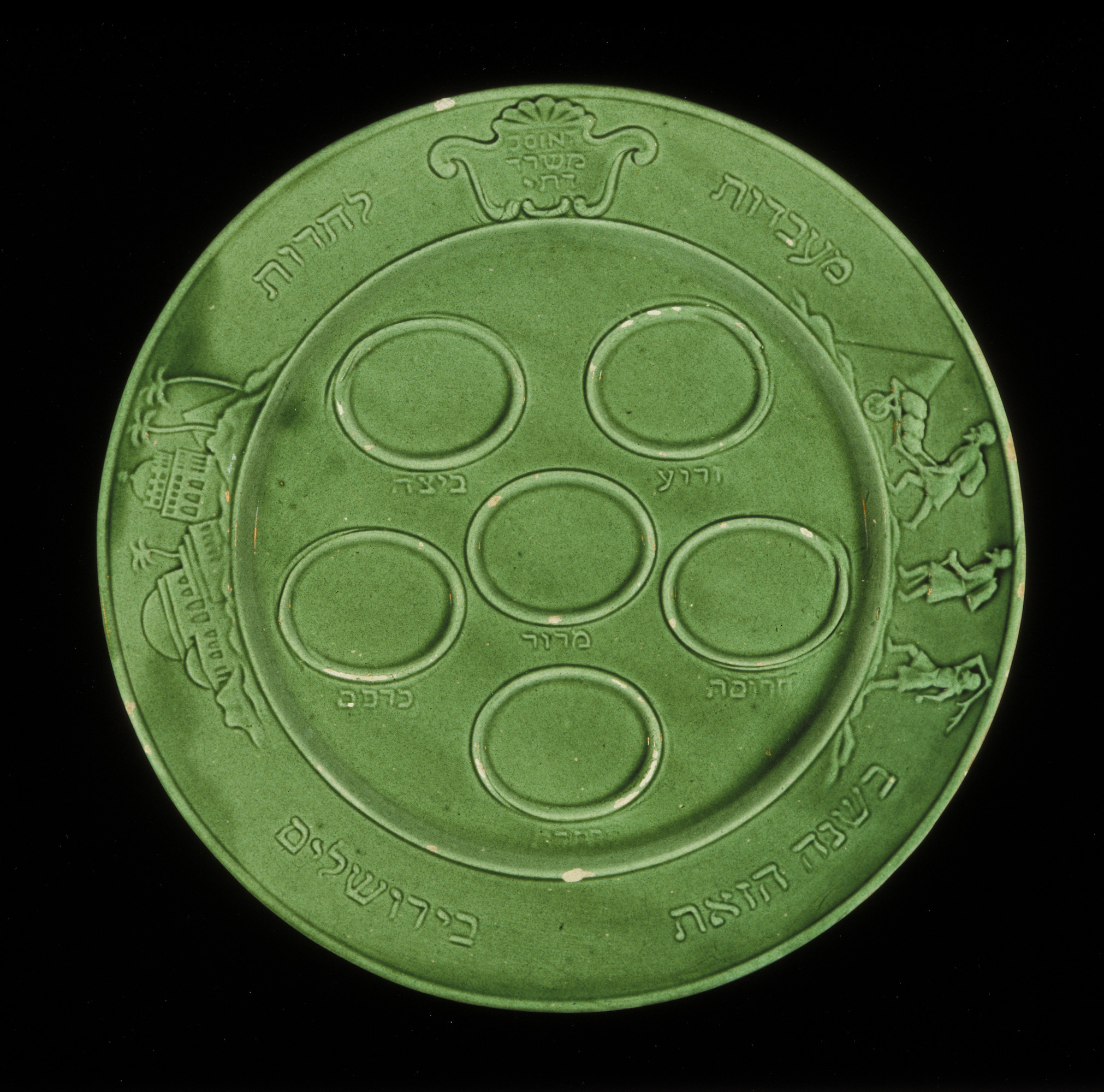 "Green glazed earthenware Passover seder plate made by Jewish DPs in the Föhrenwald displaced persons camp.  Engraved on the rim of the plate is a scene of slave laborers being forced to work by a master in the shadow of a pyramid and a group of buildings representing historic Jerusalem.  The Hebrew text on one side of the decorative motif reads: ""From Slavery to Freedom,"" and on the other: ""This Year in Jerusalem"".  Inside another decorative motif are the Hebrew and English words ""JOINT"" and ""Religious Office"".  Stamped on the back is the Hebrew term ""Sheerit ha-Pletah"" [Surviving Remnant] and the English, ""Employment Board"".  This seder plate was given to U.S. Army chaplain Rabbi Nathan Abramowitz by Jewish DPs at the Föhrenwald displaced persons camp."