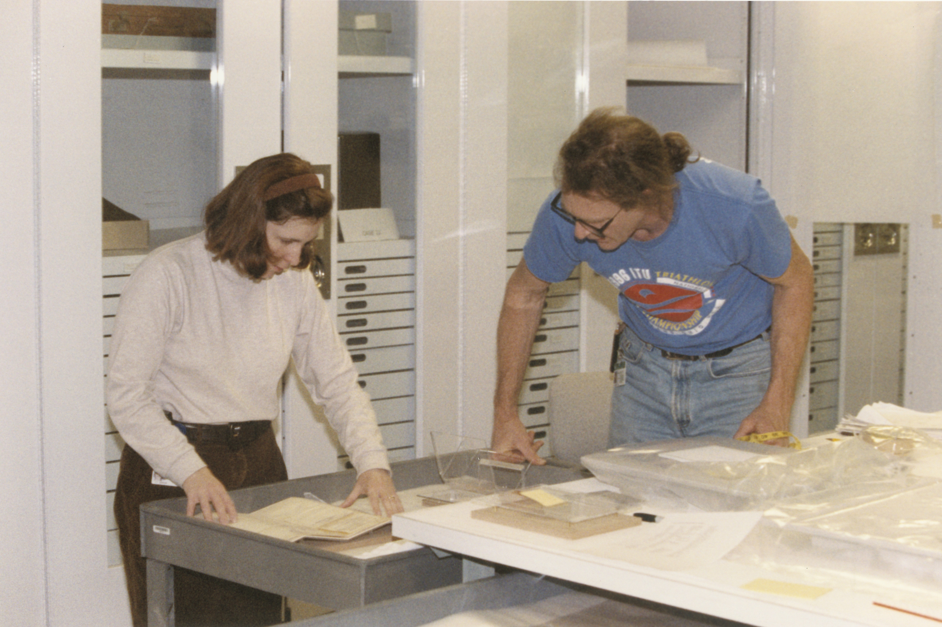 "Museum conservator Brenda Bernier, and exhibition specialist Bill Trossen, prepare documents for installation into the special exhibition ""Flight and Rescue."""