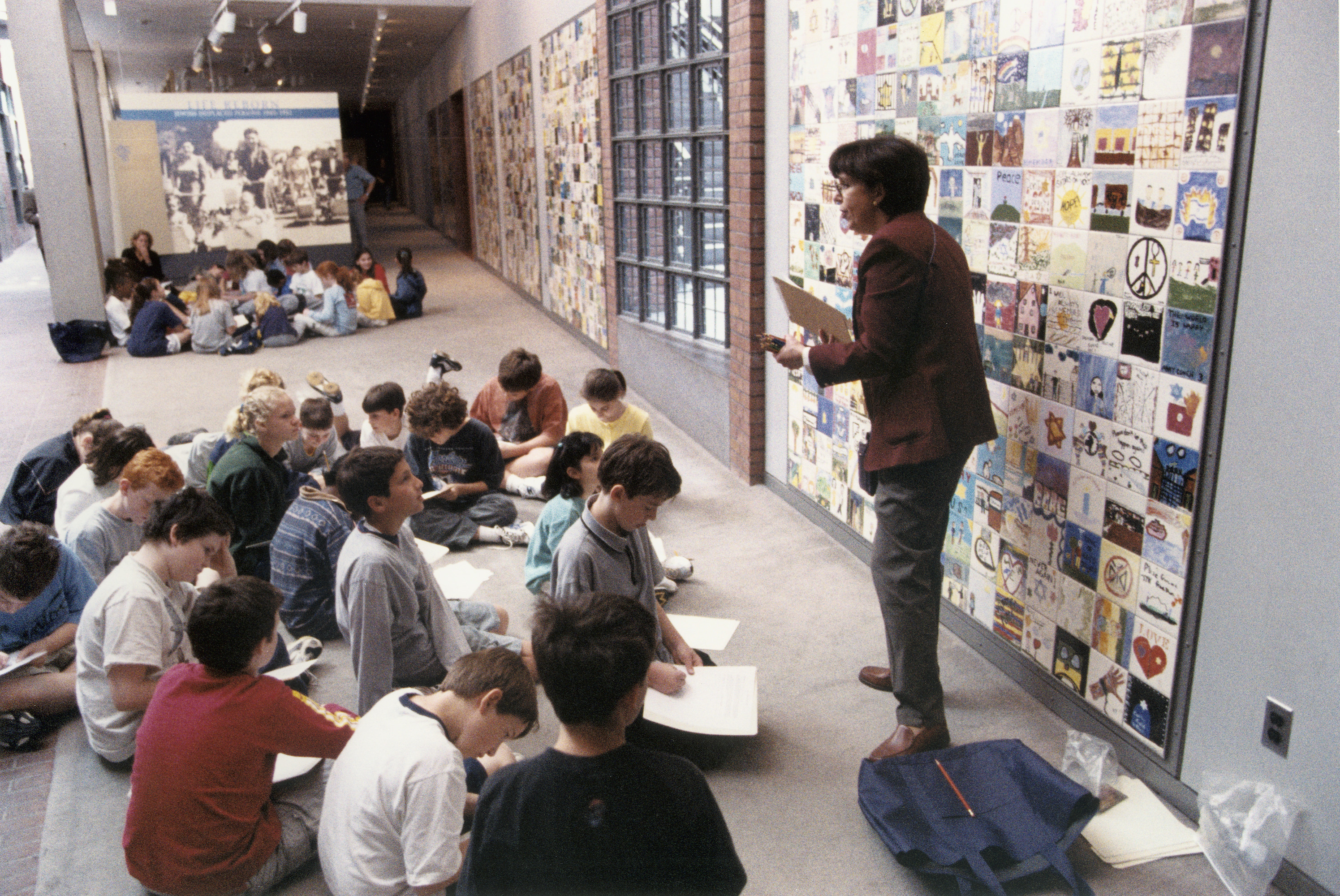 A member of the Visitors Services staff talks to a school group in front of the children's Tile Wall in the Gonda Education Center at the U.S. Holocaust Memorial Museum.