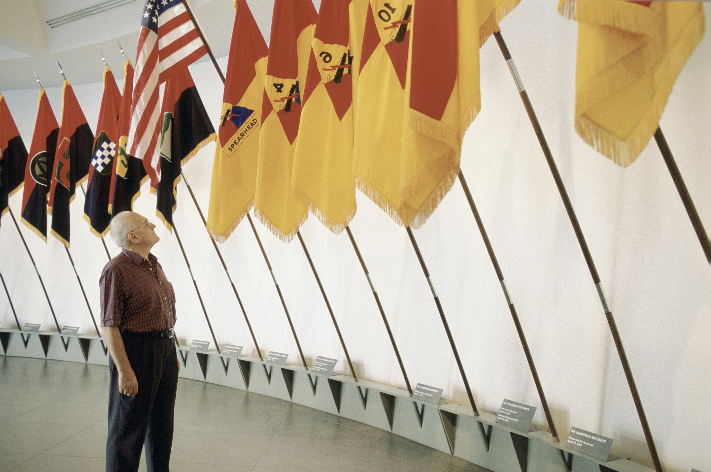 A visitor views the liberation flags installed in the lobby of the 14th Street entrance of the U.S. Holocaust Memorial Museum.
