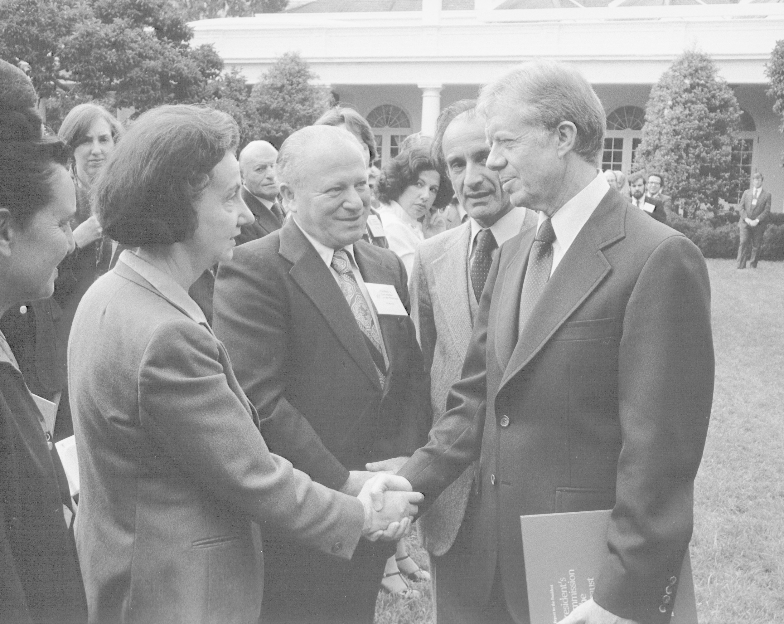 Vladka Meed shakes the hand of President Jimmy Carter at a White House Rose Garden ceremony marking the official presentation of the report of the U.S. Holocaust Commission to the president by commission chairman Elie Wiesel.   The report indicated favorable findings for the establishment of a Holocaust Memorial in the United States.  Also pictured are Benjamin Meed (second from the left) and Elie Wiesel (third from the left).