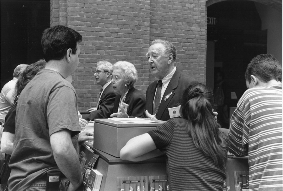Survivor volunteer Charles Stein answers questions at the information booth in the Hall of Witness at the U.S. Holocaust Memorial Museum.