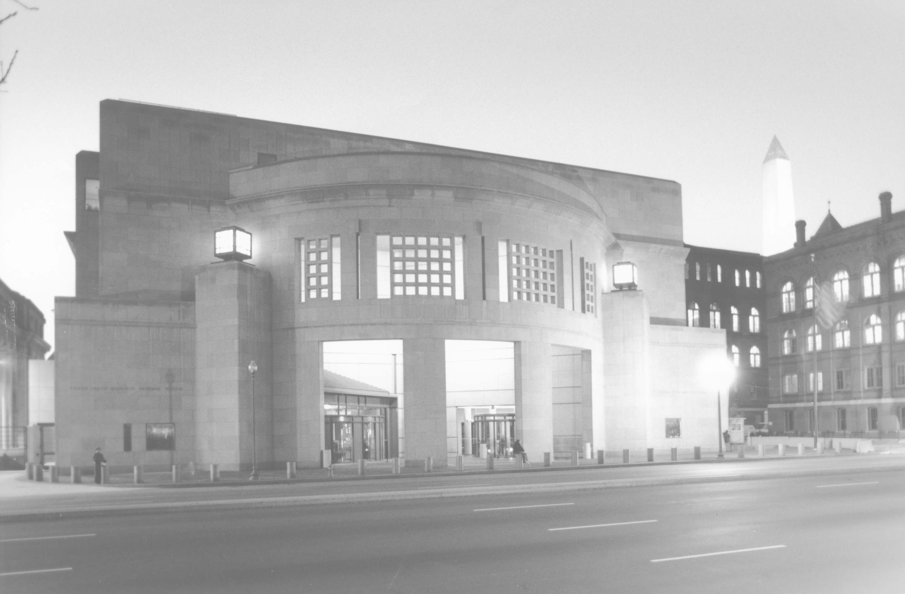 Nighttime view of the 14th Street entrance to the U.S. Holocaust Memorial Museum, with the Washington Monument in the background.