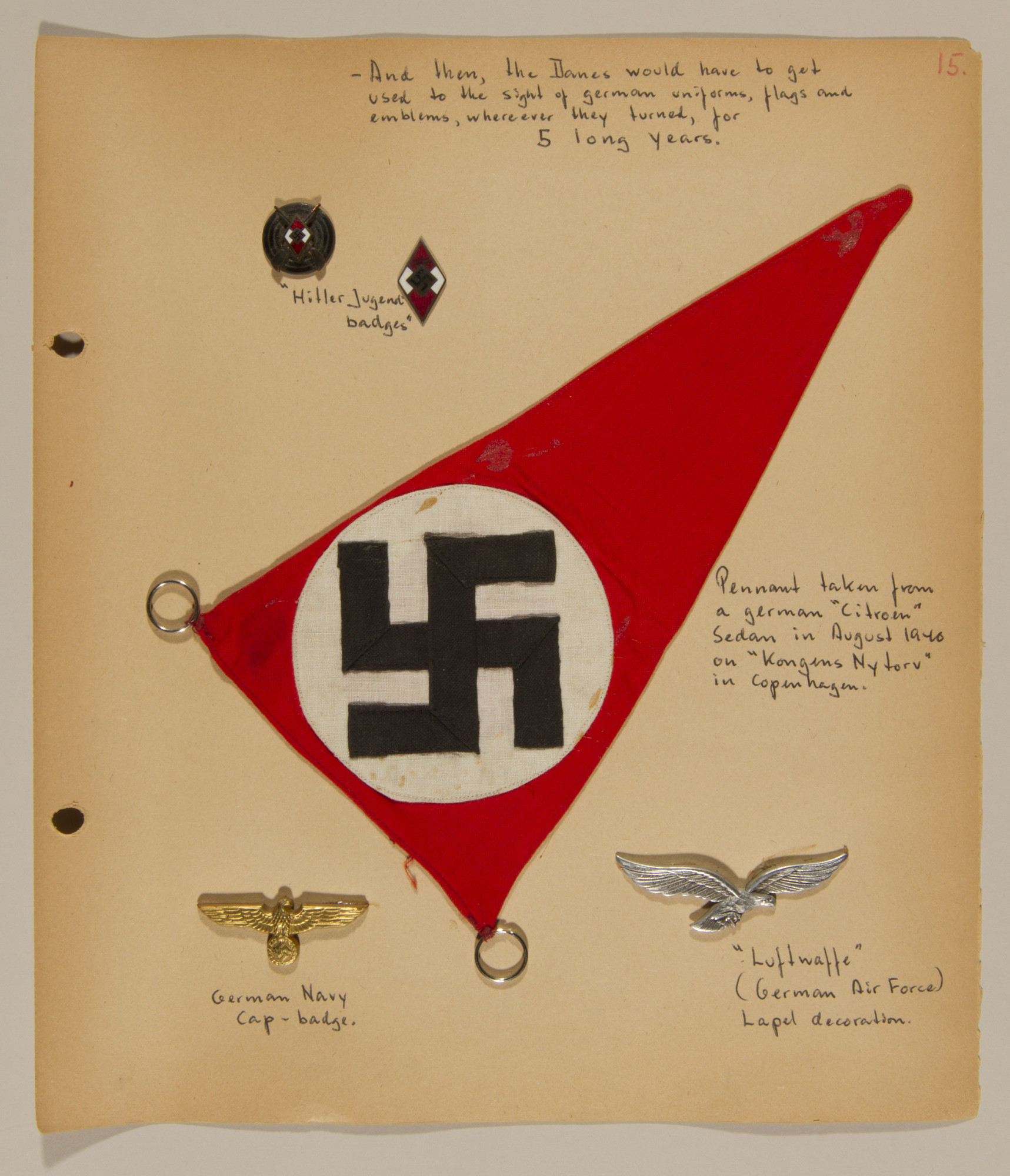 Page from volume one of a set of scrapbooks compiled by Bjorn Sibbern, a Danish policeman and resistance member, documenting the German occupation of Denmark.  This page includes three dimensional Nazi banners and pins.