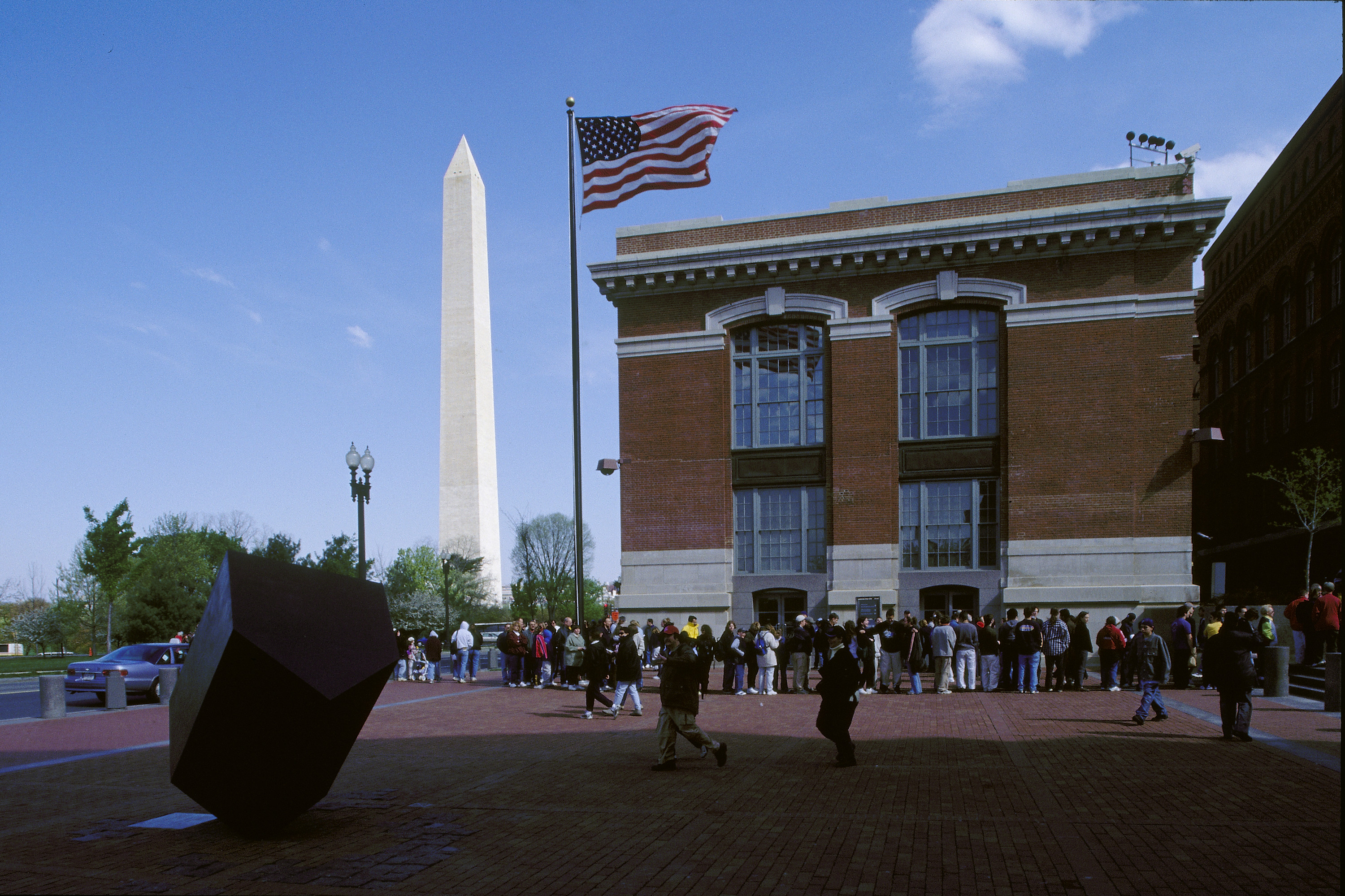 Visitors wait in line on the Eisenhower Plaza to enter the U.S. Holocaust Memorial Museum.  Behind them is the Washington Monument and the Ross Administration Building.