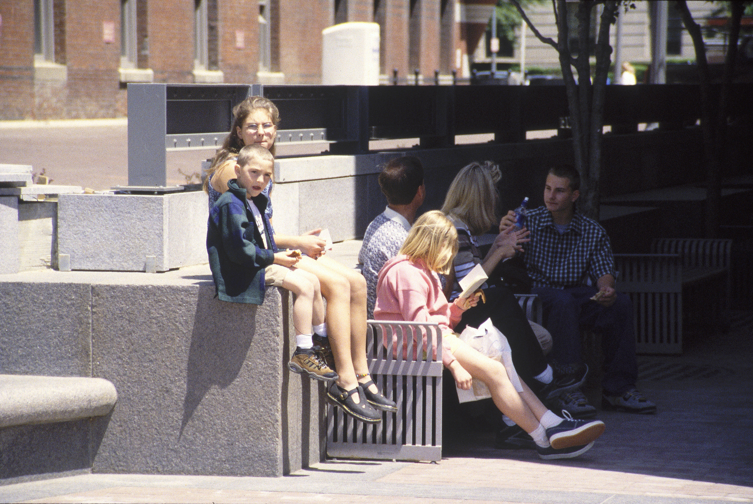 Visitors sit on benches in Thorn Alley, near the 15th Street entrance to the U.S. Holocaust Memorial Museum.