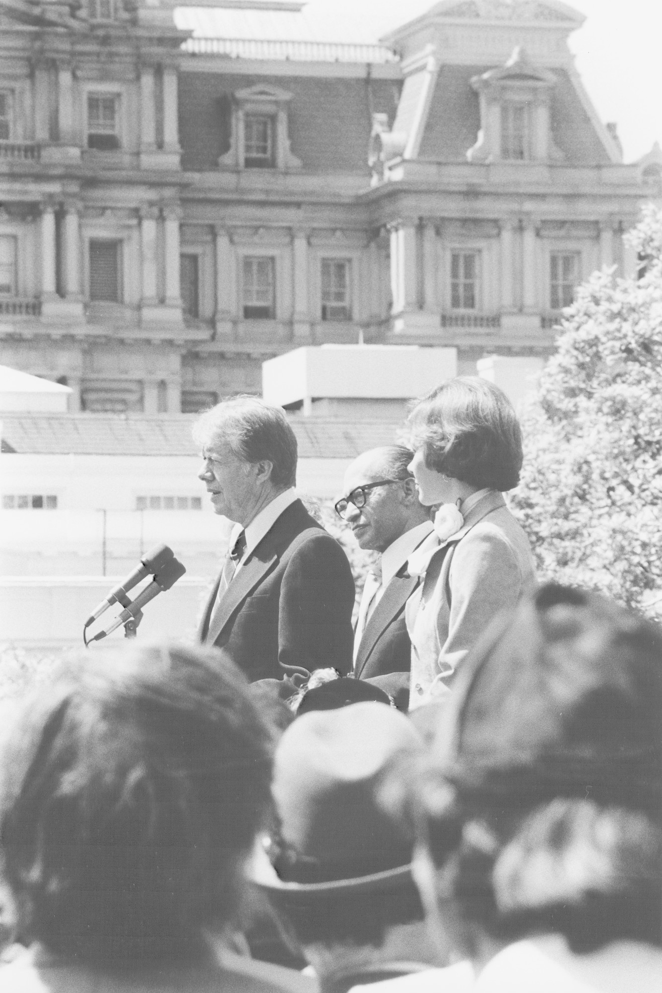 President Jimmy Carter delivers a speech at a White House ceremony marking the establishment of the Holocaust Commission.  Pictured on the podium from left to right are: President Carter, Menachem Begin and Rosalyn Carter.