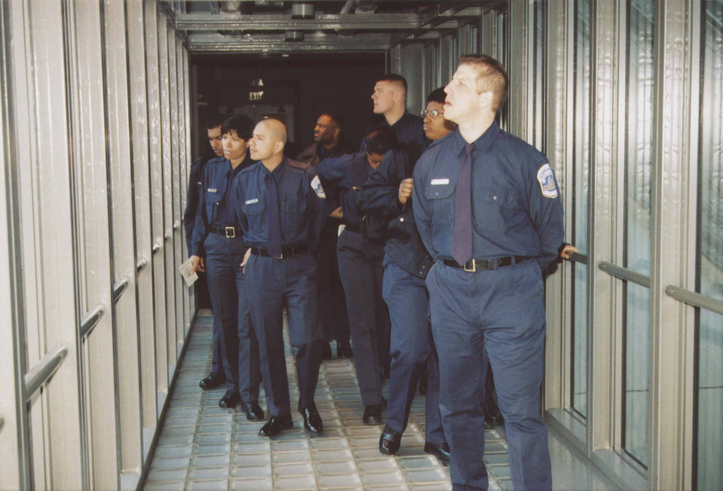 DC police training squad visits the U.S. Holocaust Memorial Museum.  Officers walk across the bridge where names of lost communities and individuals are etched in the glass while they tour the Permanent Exhibition.