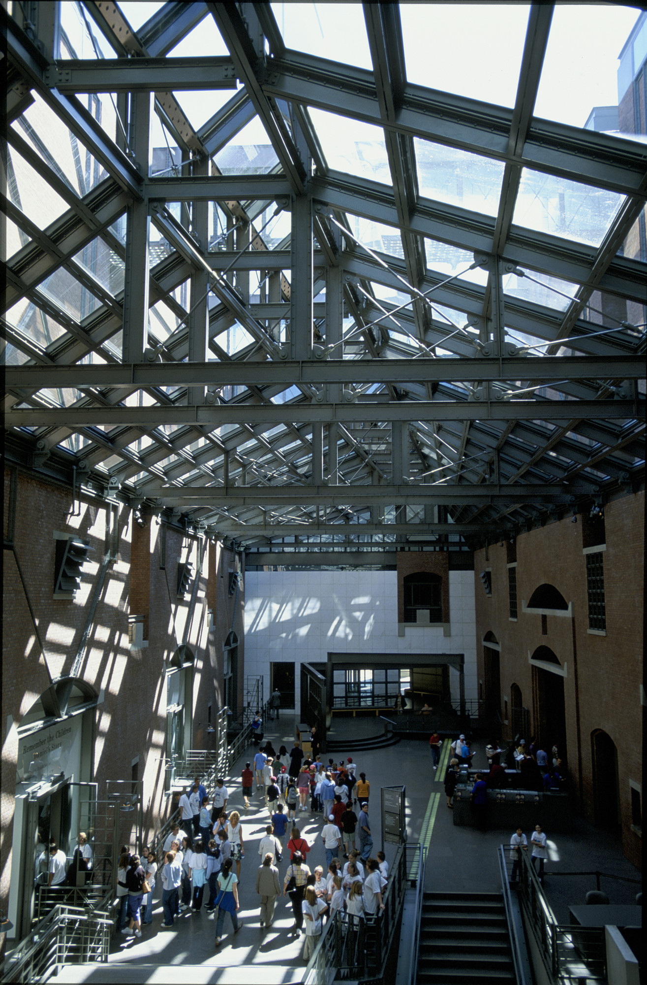 View of visitors walking through the Hall of Witness at the U.S. Holocaust Memorial Museum from the top of the staircase.