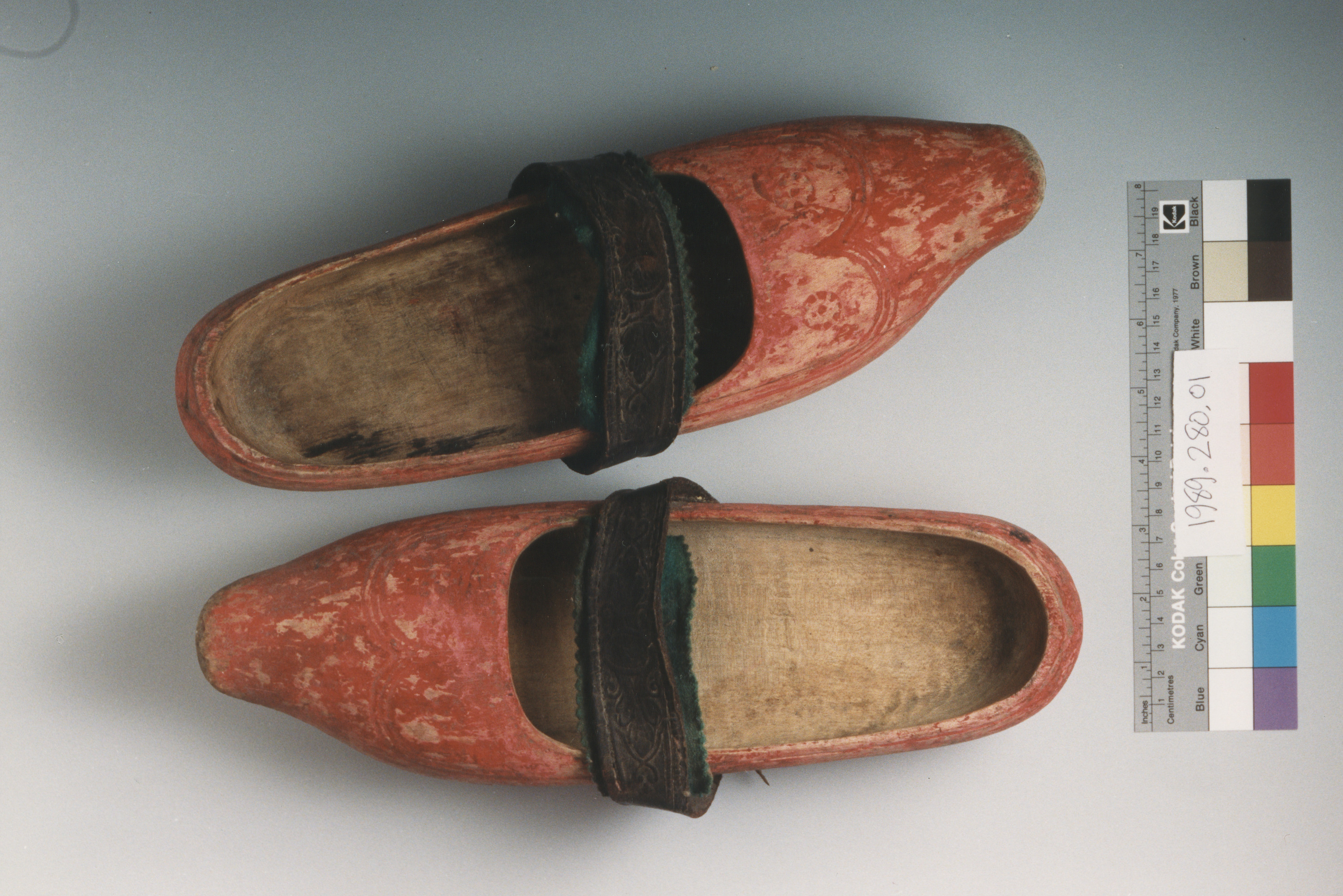 A pair of red wooden clogs similar to those worn by most residents of Le Chambon-sur-Lignon, France, as the war wore on and shoes became harder to come by.  This pair of clogs was made for the donor by her father, Samuel Heritier, who had learned a variety of useful crafts from his own father during WWI.  Unlike the clogs worn during the war by the older residents, that were blackened and then polished, the donor's clogs were tinted a bright red, as was the fashion among the young people of Le Chambon.