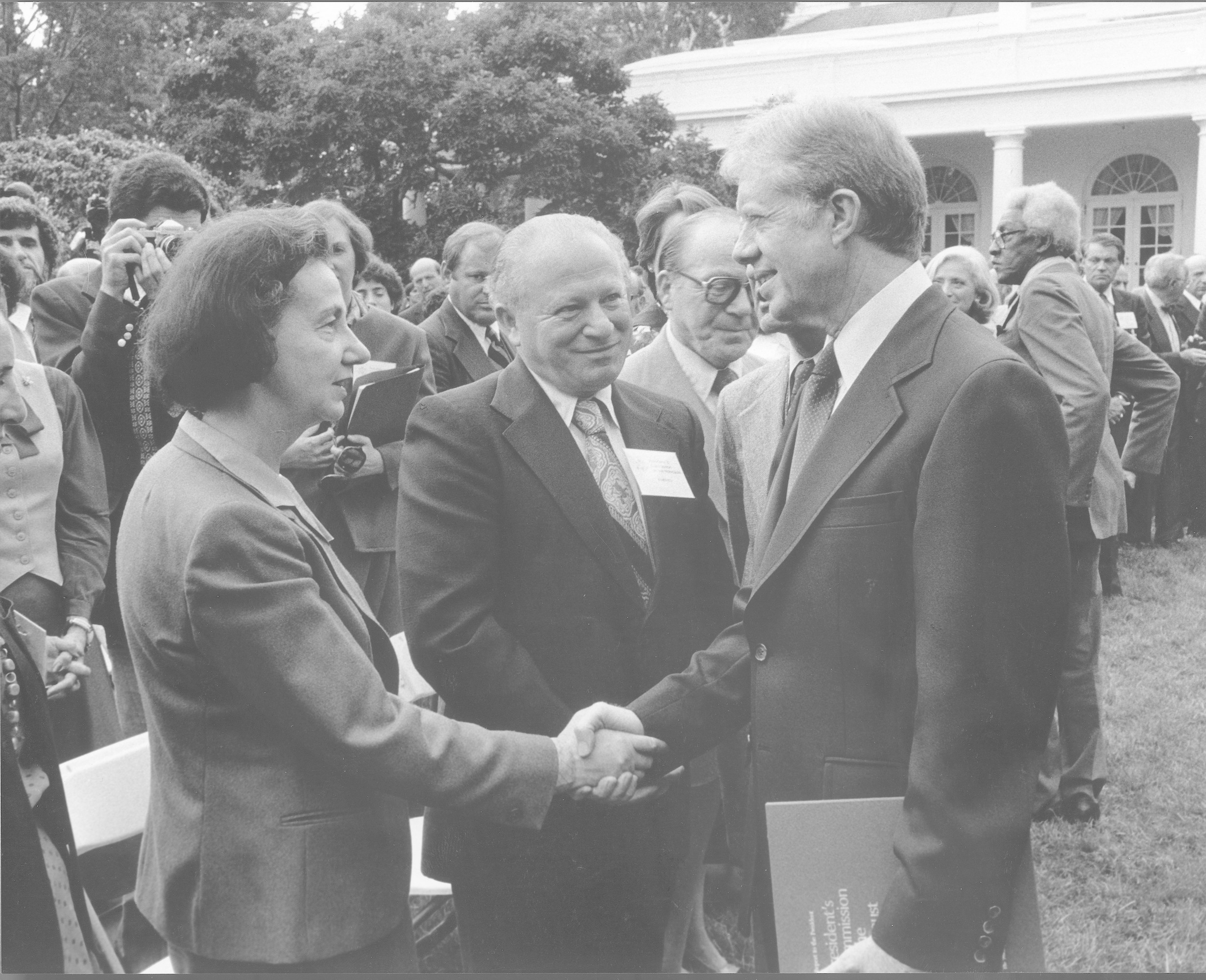 President Jimmy Carter shakes the hand of Vladka Meed during a ceremony in the White House rose garden occasioned by the formal presentation to the president of the report of the U.S. Holocaust Commission.  The report was presented by Elie Wiesel.  Pictured in the foreground from left to right are: Vladka Meed, Benjamin Meed and President Jimmy Carter.