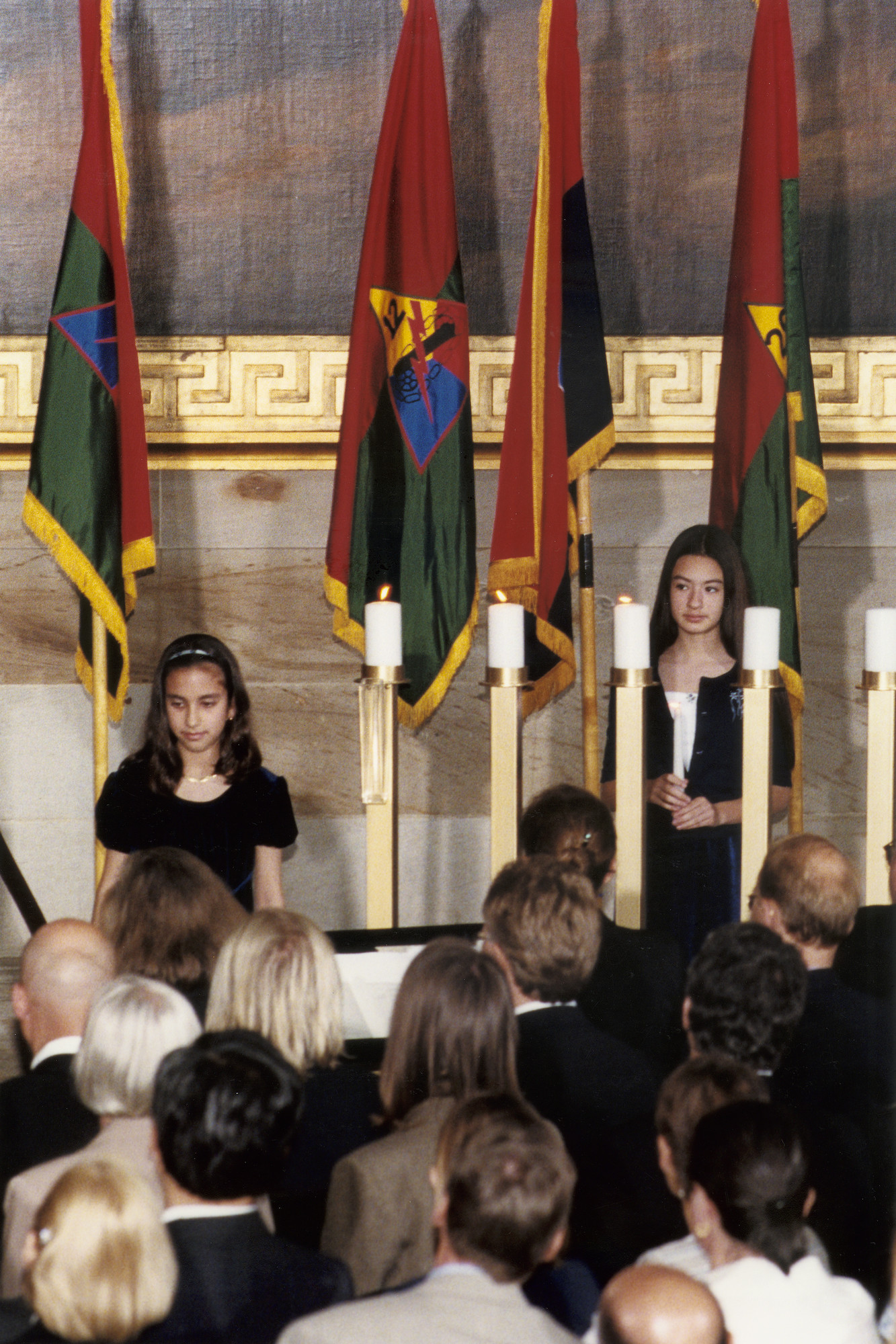"Amanda Nickels (left) and Leah Katz-Hernandez (right) assist the candlelighters at the 2000 Days of Remembrance ceremony in the capitol rotunda.   Amanda's participation is in memory of the Sinti and Roma victims of the Holocaust; Leah's participation is in memory of the mentally and physically handicapped victims of the Holocaust.   The theme of this year's commemoration was ""The Holocaust and the New Century: The Imperative to Remember.""  Swedish Prime Minister Göran Persson delivered the keynote address, and Nobel laureate Elie Wiesel and U.S. Secretary of the Treasury Stuart E. Eizenstat were recognized for their extraordinary contributions."