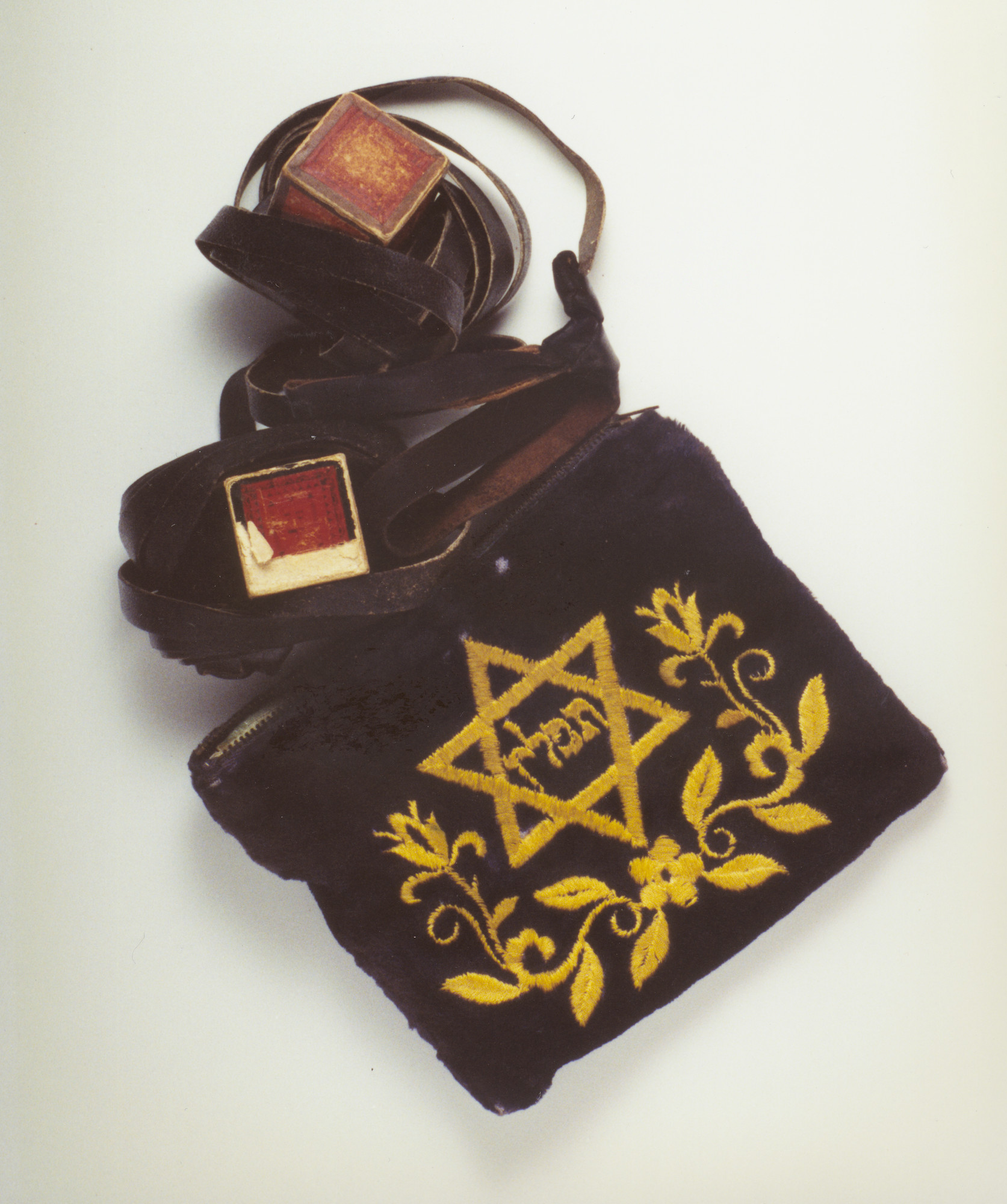 A set of Jewish ritual phylacteries (tefillin) and a gold velour tefillin bag.  The donor, Walter Fried, found this artifact on the body of a concentration camp prisoner buried in a grave near Regensburg.  The prisoner had died during a death march.