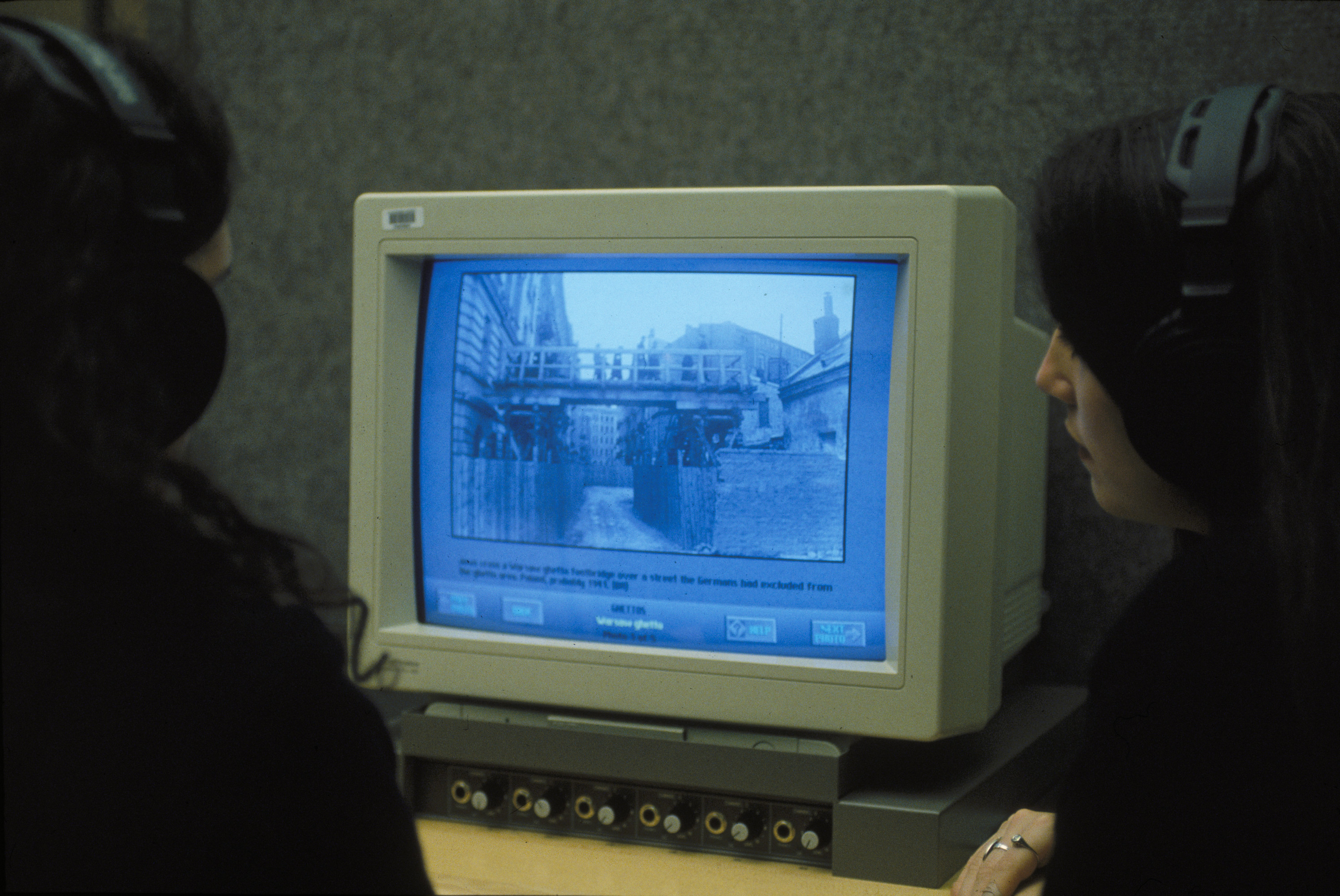 Two visitors in the Wexner Learning Center of the U.S. Holocaust Memorial Museum view a computer monitor displaying images from the Warsaw ghetto.