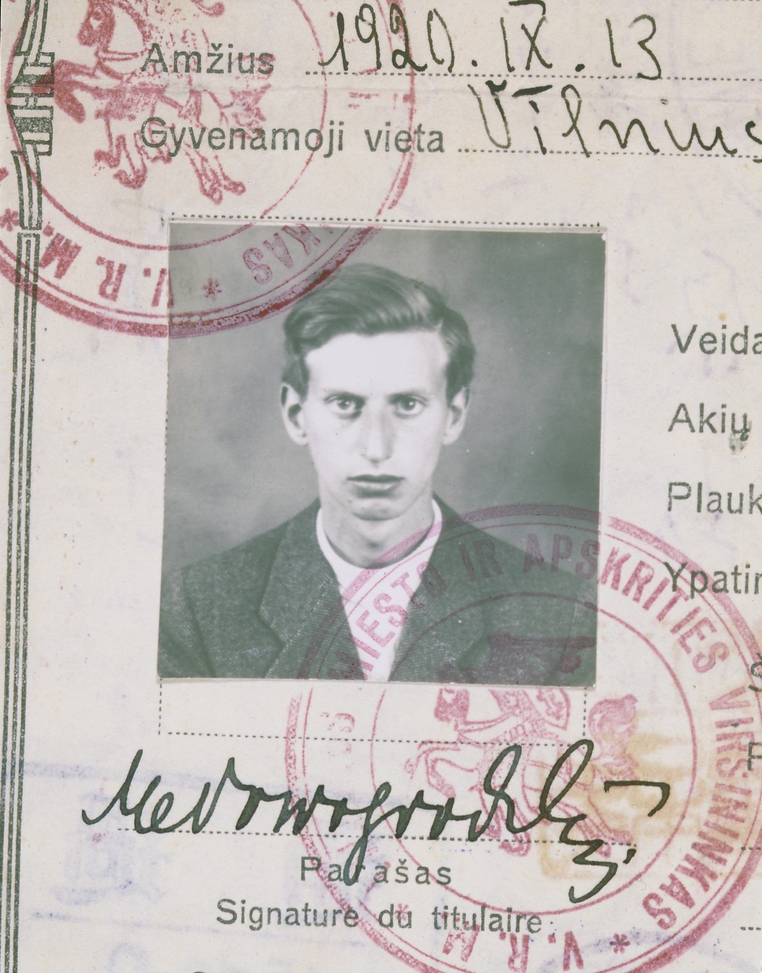 "A closeup of the identification photograph adhered to the Lithuanian Safe Conduct Pass issued to Markus Nowogrodzki. This pass was eventually bound into a passport. It contains Sugihara ink stamps, two Russian transit visas, a Lithuanian stamp, an American non-immigration visa, and a Seattle entry stamp.  Sugihara visa (center left) issued with a legitimate emergency (""non-immigration"") visa for the U.S. (bottom, far left) obtained in Kaunas in July 1940, one of only a few dozen U.S. visas issued before the consulate closed in mid-August, 1940."