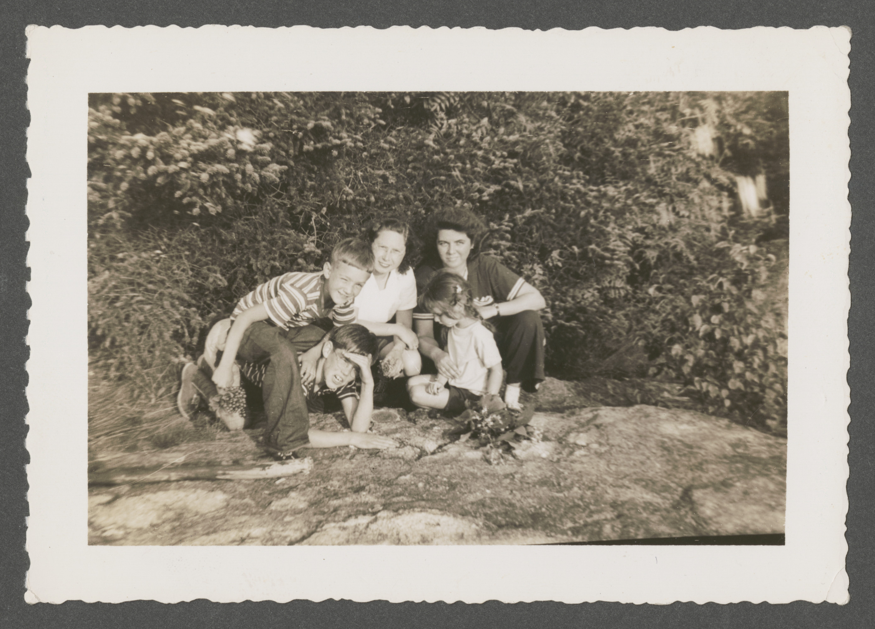 "Goldschmied and Sharp family members relax on the peak of Mount Sunapee in New Hampshire.  Pictured is Renee Goldschmied (back, center), with Martha Sharp (back, right) and [probably] her children Hastings (front, on hands and knees) and Martha Content (front, right).    The inscription on the back of the photograph reads, ""Renee on peak of Mount Sunopee, 1214 ft. high, summer 1942 (Sharps)."""