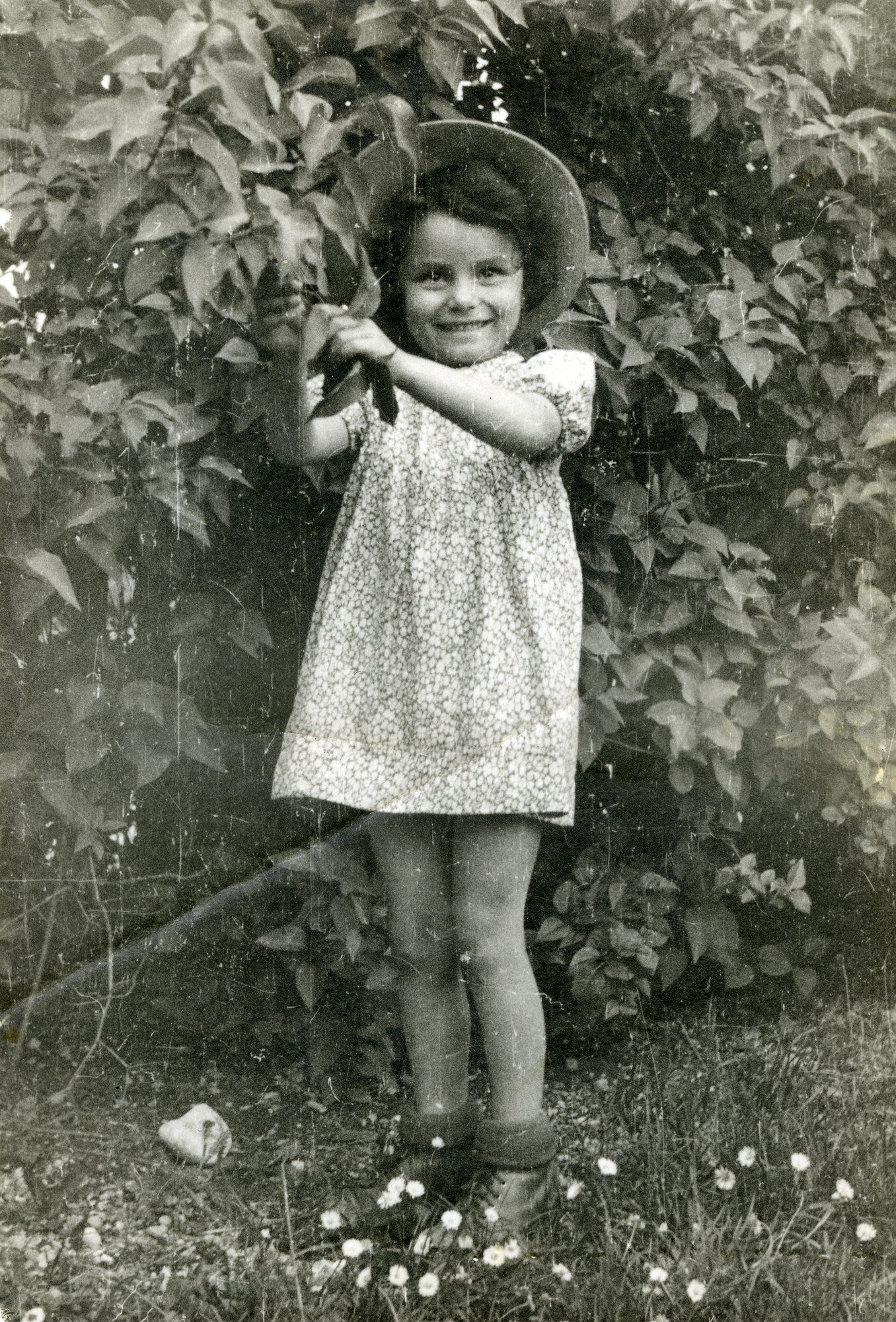 Basia Szrajer stands in a garden, probably in the Neu Freimann displaced persons camp.