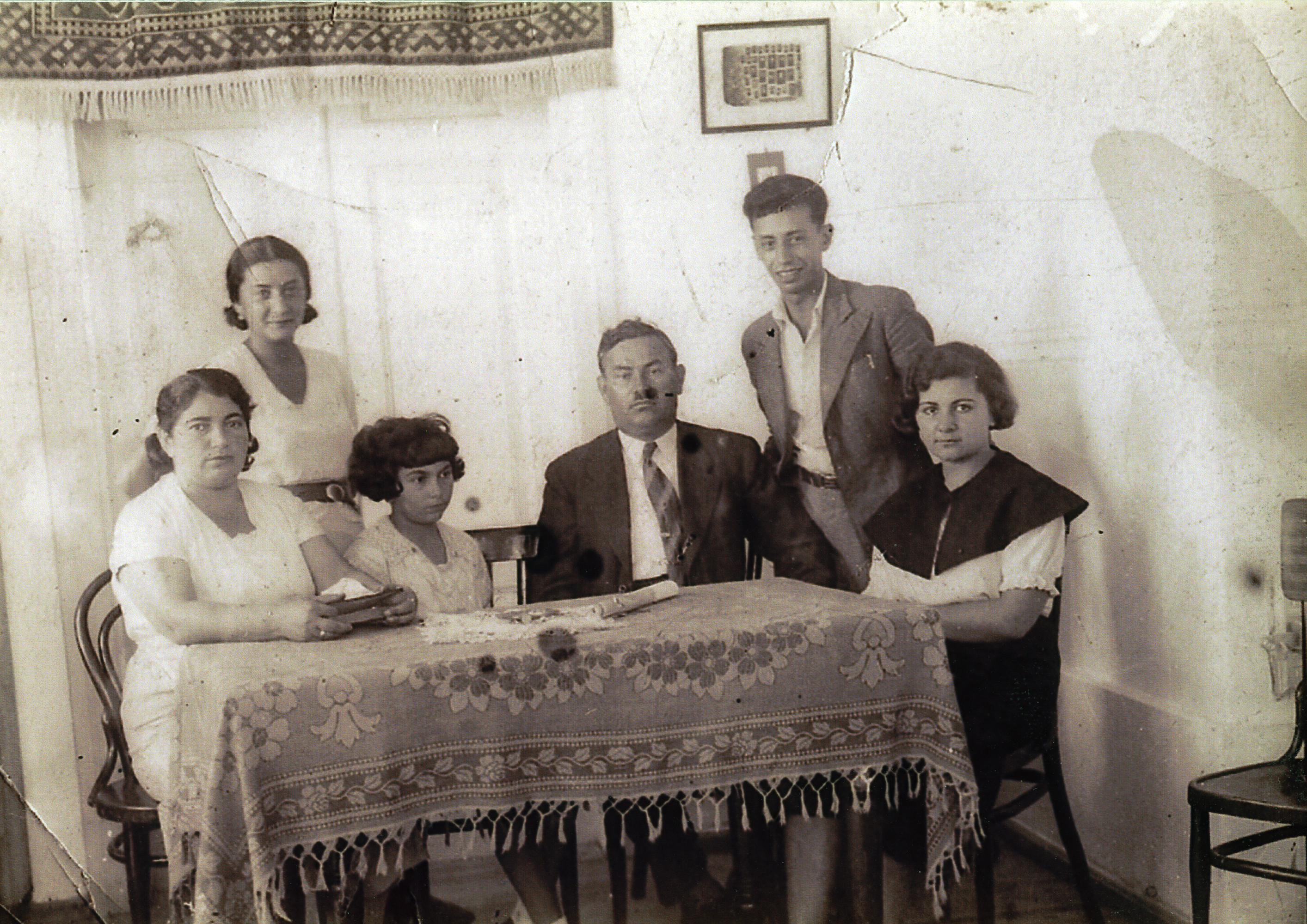 The Goldschmidt family poses around a table.  Riva Szrajer  (nee Goldschmidt) is standing behind the chairs (left). Mordechai Goldschmidt is standing behind the chairs (right). Their father, Moshe Goldshmidt, is sitting at the table (second from the right).