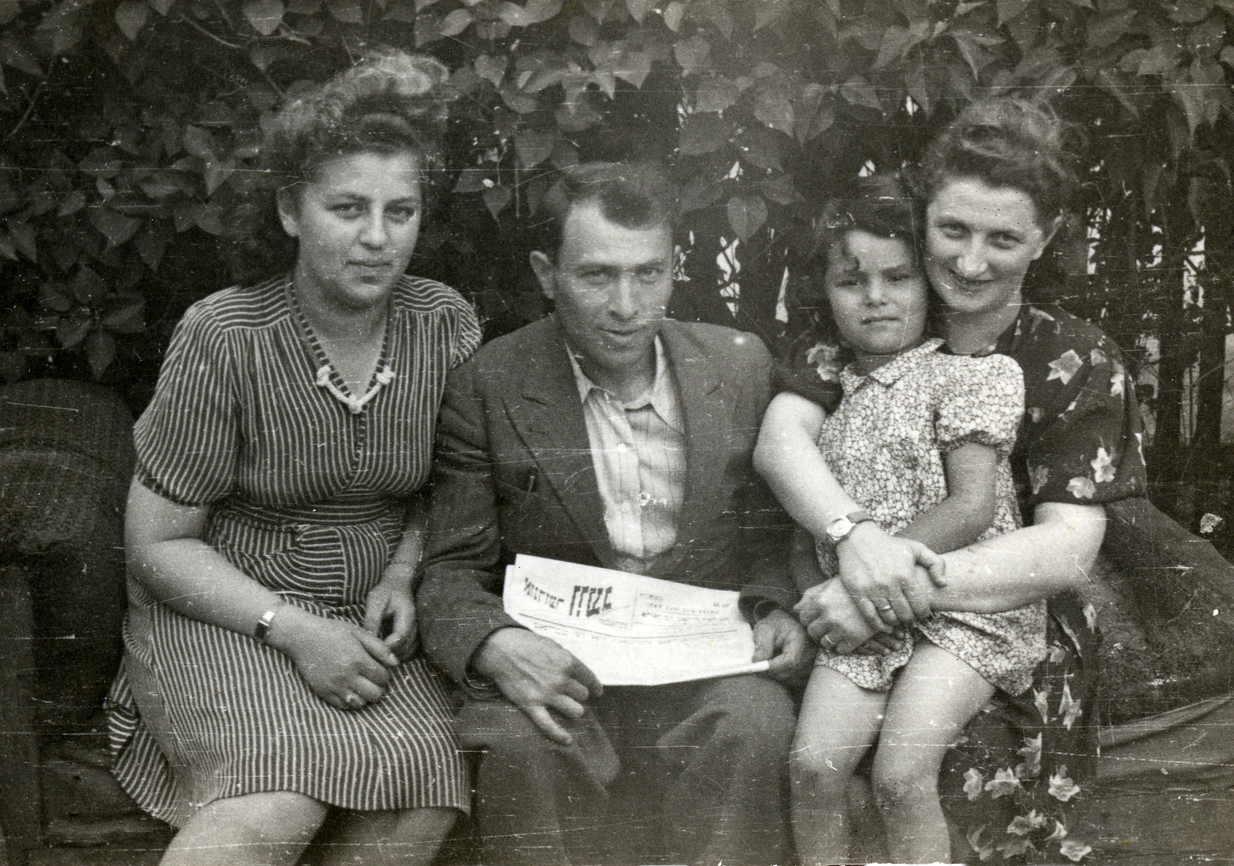 Basia Szrajer dsits on the lap of Rosa Pick, a survivor from her hometown in Poland.   Rosa's husband Max is in the center with a newspaper and an unidentified woman is on the left.