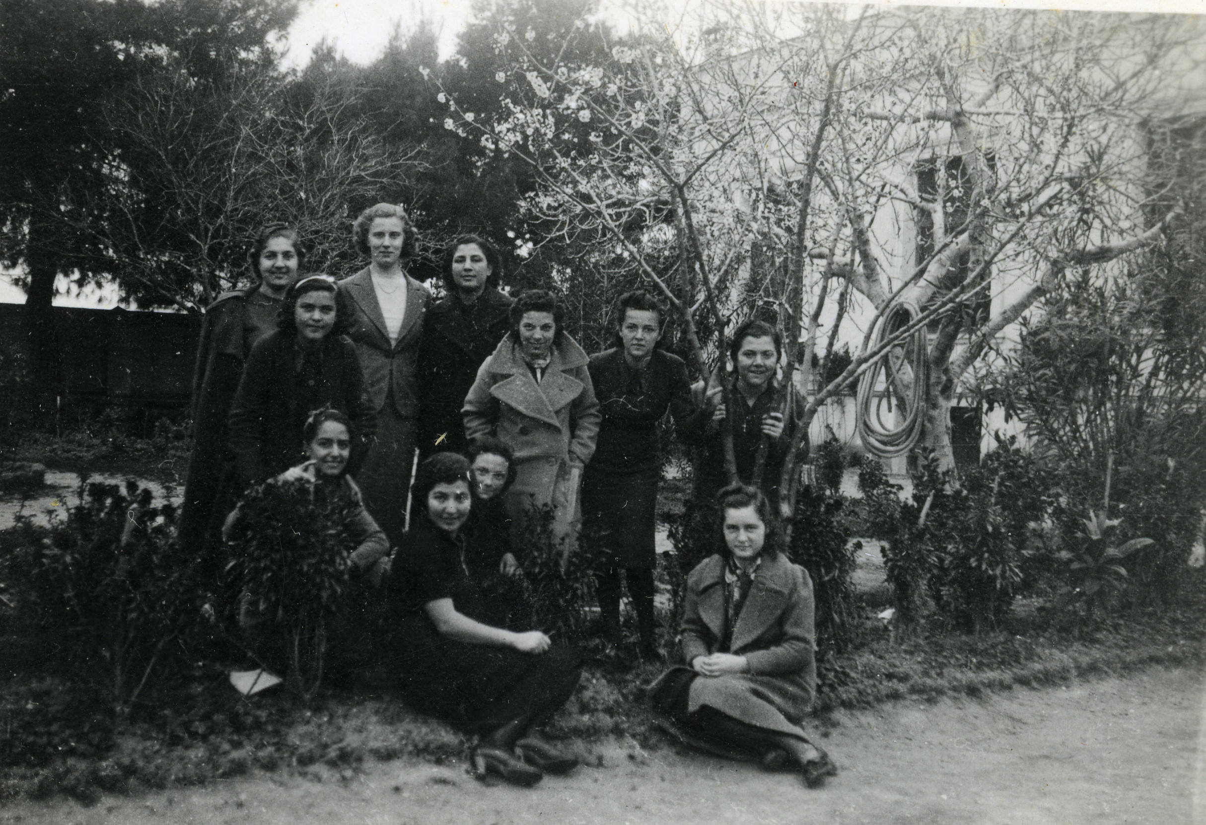 Group photo of fourth class girls, taken in the school garden with Miss Peck, in Salonika in March 1939.  Jenny Ezratty is third from the left, sitting doown, behind a classmate.