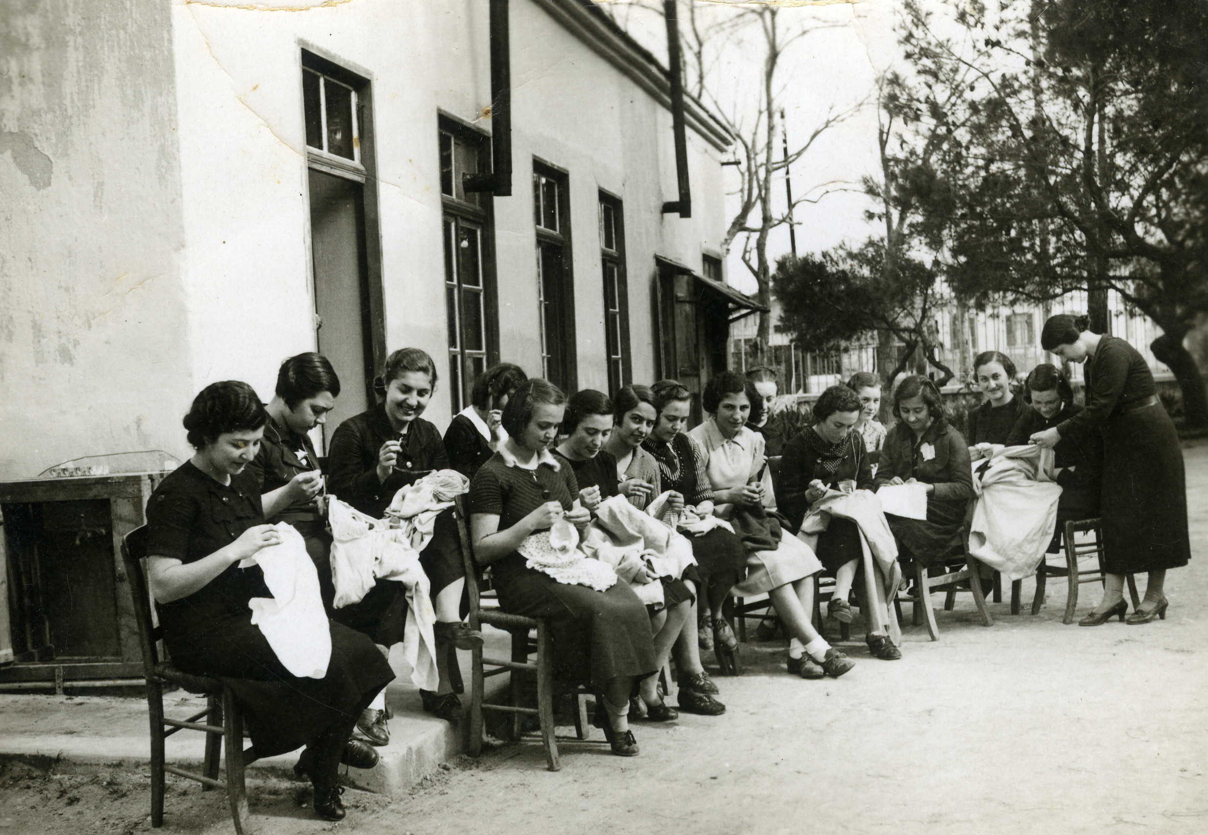 Young women in a sewing and embroidery class with  Miss Asperidov work outside.