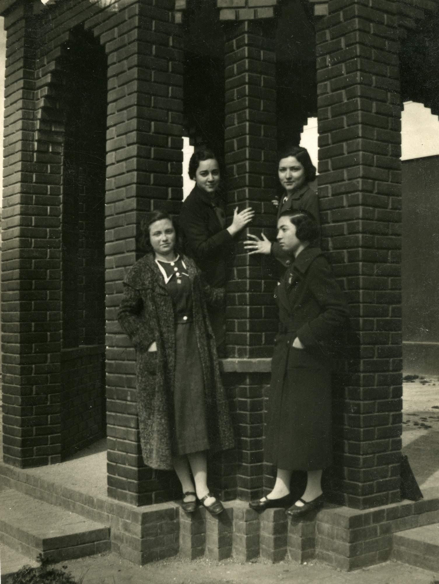 Four young women stand on the ledge of a brick structure under the bridge, in Salonika in 1940.  Jenny Noam (nee Ezratty) is standing in the front row on the left.