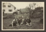 Five friends sit in a field across from an army  truck [probably in the Weilheim displaced persons camp].