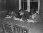 Three young survivors study at a table in the Hadamar Institute.
