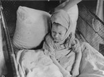 A sick child sits in a crib in the Kovno ghetto hospital, covered by a blanket with a Star of David.