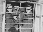 Three men behind a barred window in the ghetto jail.
