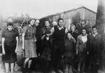 Group portrait of survivors of the Klooga concentration camp in front of a barracks.