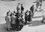 "Jews converse outside in the ""Sammelstelle"" [gathering place] in the Kovno ghetto."