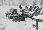 Household furnishings left outside on the street in the Kovno ghetto are covered with snow.