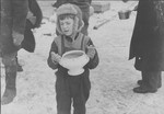 A young boy carrying a bowl of soup, holding food ration tickets.