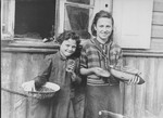 Two young girls stand outside a house in the Kovno ghetto holding bread and bowls of food.
