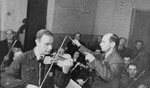 Performance of the Kovno ghetto orchestra.   Pictured are Boris (Abraham, or Abrasha for short), Stupel, playing the violin and Michael Leo Hofmekler, conducting.
