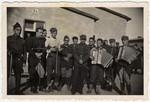 Group portrait of Polish prisoners-of-war holding musical instruments.