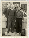 Four cousins pose in front of a memorial at the Leipheim displaced persons camp.