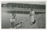 Misa Grunwald catches a fish in a net.  Standing to the side are his step-mother Melitta Grunwald, and an unidentified gentleman who provided the family with a fake passport, allowing them to escape from Czechoslovakia.