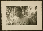 A profile view of Jesse Owens wearing his USA Olympic tracksuit.