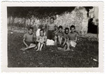 A group of children sit with their female guardian at the children's home Chateau de la Hille.