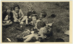 """Young children enjoy an ice cream picnic.  David Marcus' original caption reads: """"Ice cream, dougnuts, and happy faces."""""""